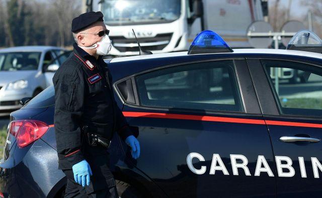 Italijanski karabinjer z masko na policijskem kontrolnem mestu nekaj kilometrov od kraja Castiglione d'Adda, jugovzhodno od Milana. FOTO: Miguel Medina/Afp