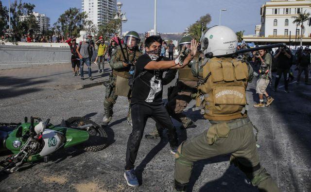 Protivladni protesti v Čilu se nadaljujejo tudi letos. Na fotografiji spopad policista in protestnika v letovišču Vina del Mar. FOTO: Javier Torres/AFP