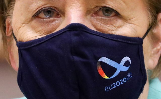 German Chancellor Angela Merkel wears a protective face mask with the logo of Germany's EU council presidency as she attends a plenary session in Brussels on July 8, 2020, upon the presention of the German programme for EU presidency. - The German presidency started on July 1, and will last until December 31, 2020. (Photo by YVES HERMAN / POOL / AFP) Foto Yves Herman Afp
