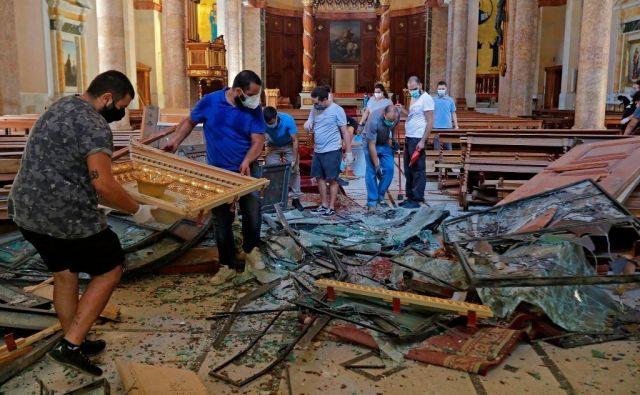 Tudi sakralna arhitektura v Bejrutu je poškodovana. V maronitski cerkvi svetega Jurija so takole reševali opremo. Foto Joseph Eid/AFP
