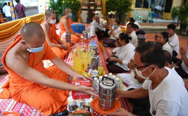 V pagodi v Phnom Penhu menihi sprejemajo hrano. FOTO: Tang Chhin Sothy/AFP