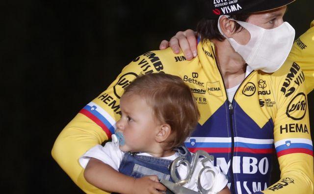V nedeljo popoldne, ko je sonce nad Parizom že zahajalo in so se vsi junaki Toura izmenjali na zmagovalnem odru, je v naročju očka prišel tudi on. FOTO : Reuters
