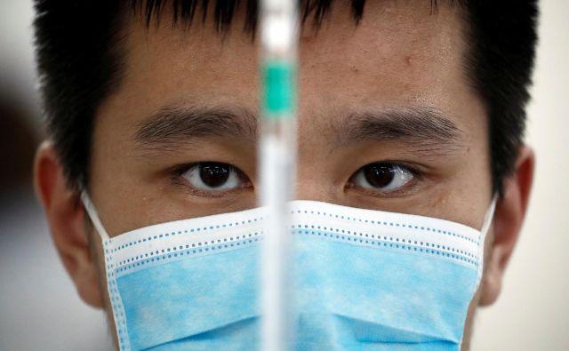 Proti covidu-19 so »po hitrem postopku« cepili najmanj 350.000 Kitajcev, in to s tremi cepivi, ki so še v razvoju. FOTO: Thomas Peter/Reuters