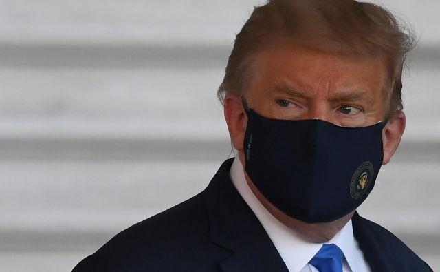 Donald Trump si je na poti v bolnišnico s helikopterjem Marine One nadel zaščitno masko.FOTO: Saul Loeb/AFP
