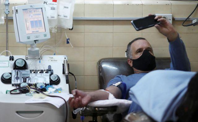 Argentinec, ki je okreval po okužbi, med doniranjem krvi na inštitutu v La Plati v Argentini. FOTO:Agustin Marcarian/Reuters