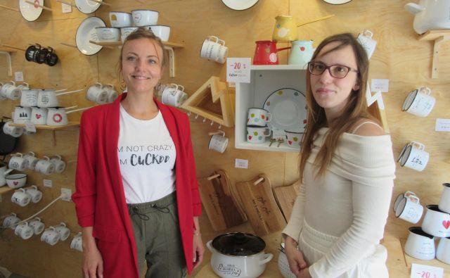 Sestri Nina Majcen (levo) in Urška Golob v Kukušnjaku, kjer so na voljo vsi izdelki iz emajla, lesa ter drugih materialov. Izdelkov je vsak dan več. FOTO: Špela Kuralt/Delo