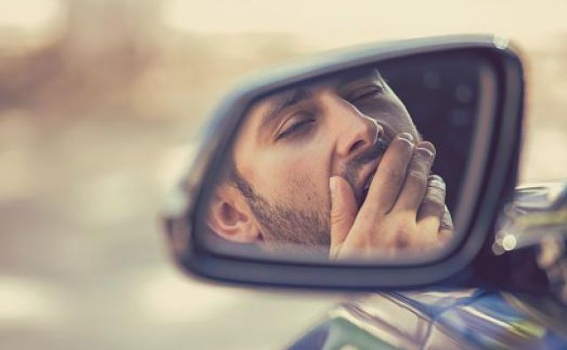 Side mirror view reflection sleepy tired fatigued yawning exhausted young man driving his car in traffic after long hour drive. Transportation sleep deprivation accident concept Foto Siphotography Getty Images/istockphoto