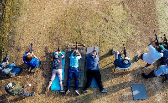 Študenti streljajo iz polavtomatskih pušk AR-15 med tečajem streljanja na akademiji za strelno orožje Boondocks v Jacksonu v Mississippiju. Prodaja orožja in zanimanje zanj sta se po celotnih ZDA v zadnjem obdobju še dodatno povečali, razlog za to pa so pandemija, protesti in politika. FOTO: Chandan Khanna/Afp